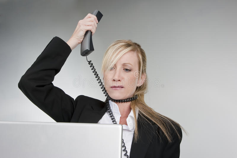 Customer Service. A female customer service agent shows her frustration with the telephone and computer stock photography