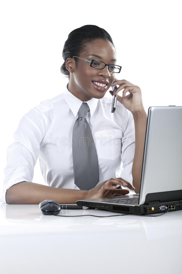 Customer service. Beautiful black businesswomen in front of her computer at the office talking on the phone stock image