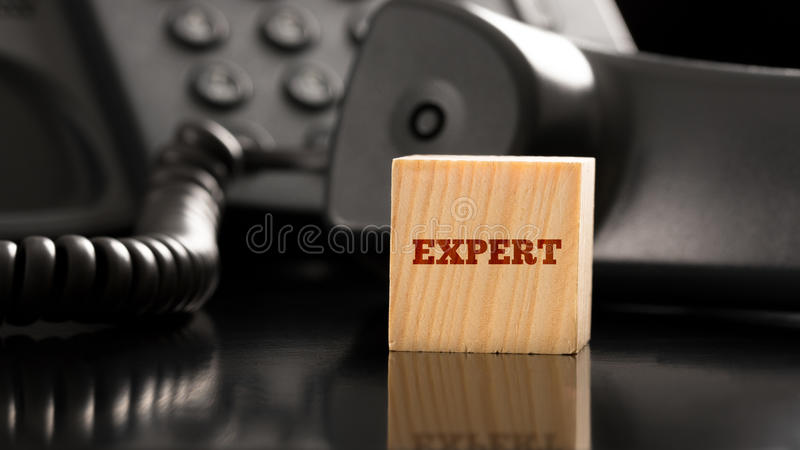 Customer service with advice and help from an expert. Wooden cube with an Expert sign on it next to a landline telephone. Conceptual of professional and accurate royalty free stock photo