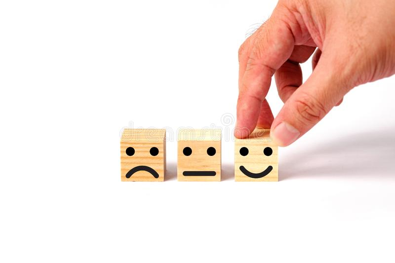Customer service evaluation and satisfaction survey concept. Customer service evaluation and satisfaction survey concept with wooden blocks and human hand royalty free stock images