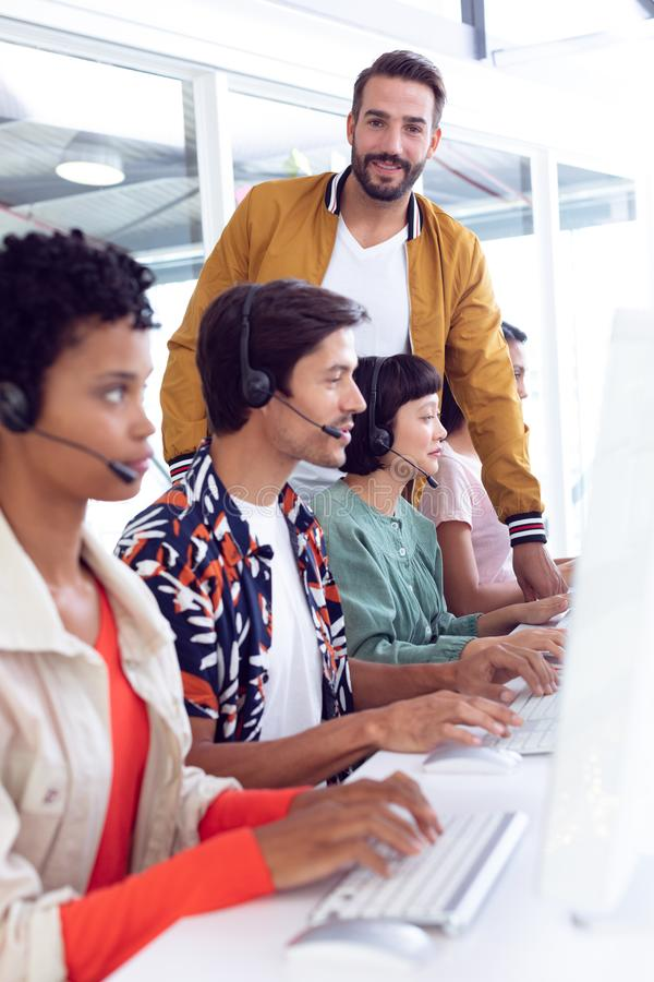 Customer service executive trainer assisting her team at desk in office. Side view of diverse customer service executive trainer assisting her team at desk in royalty free stock photo
