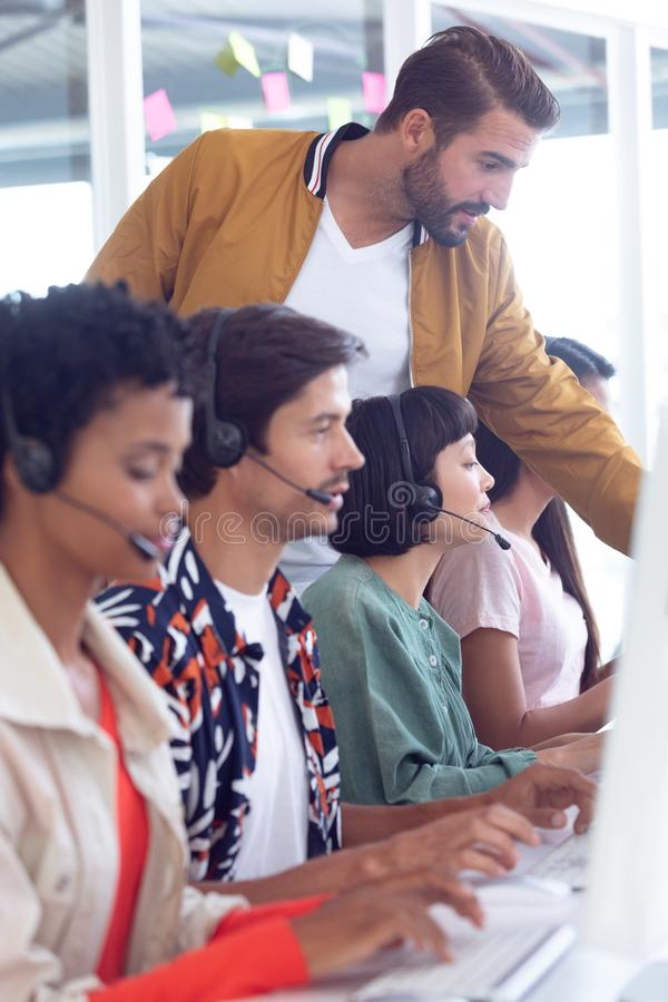 Customer service executive trainer assisting her team at desk. Side view of diverse customer service executive trainer assisting her team at desk in office royalty free stock image