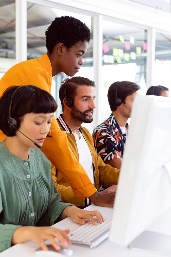 Customer service executive trainer assisting her team at desk. Side view of diverse customer service executive trainer assisting her team at desk in office stock photos