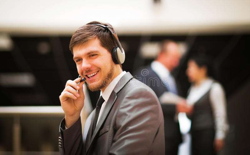Customer service operator talking on headse. Young customer service operator talking on headset, smiling stock images