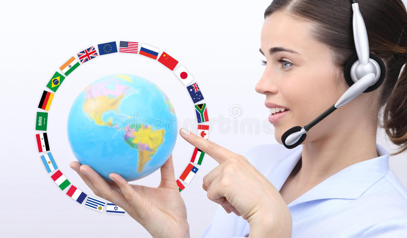 Customer service operator woman with headset pointing her finger. With globe and flags isolated on white background royalty free stock photo