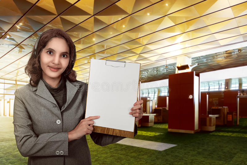 Customer service operator woman with headset smiling show empty. Paperboard. You can put your design on the board royalty free stock image