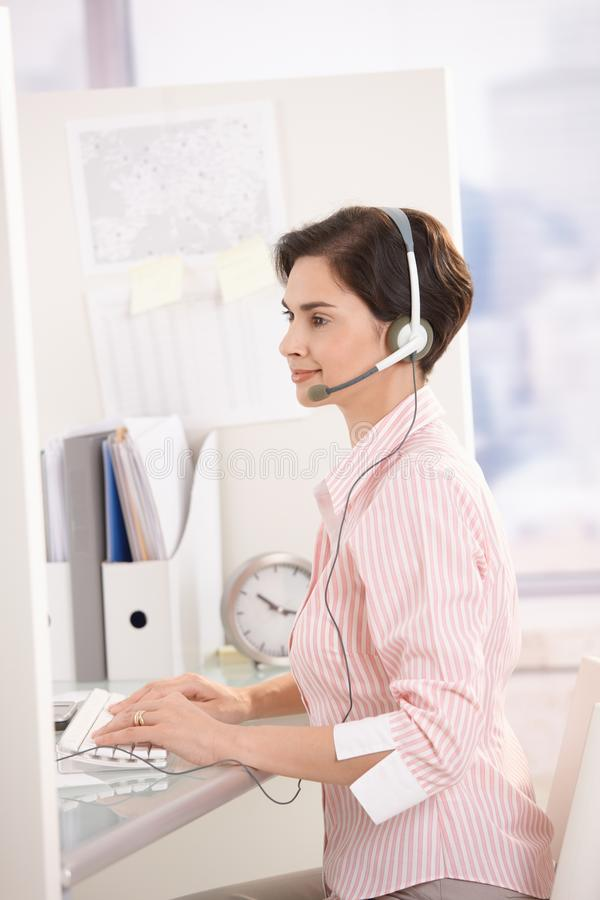 Customer service operator at work. Smiling customer service operator at work, sitting at desk, using computer and headset stock photos