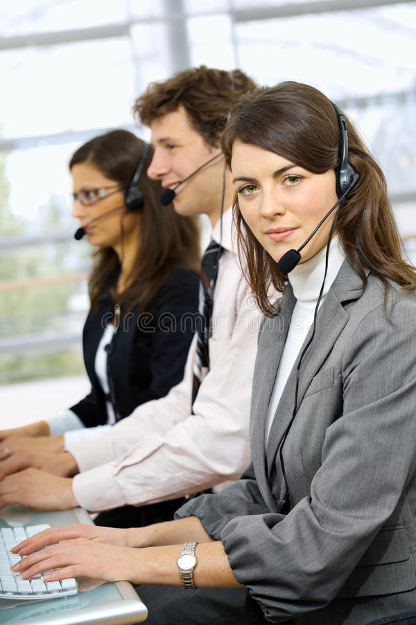 Customer service operators. Three young customer service operators sitting in a row and talking on headset. Selective focus on women in front royalty free stock image