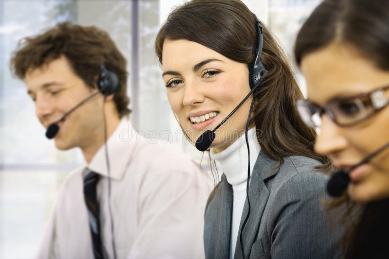 Customer service operators. Three young customer service operators sitting in a row and talking on headset. Selective focus on women in middle. Isolated on white stock photography