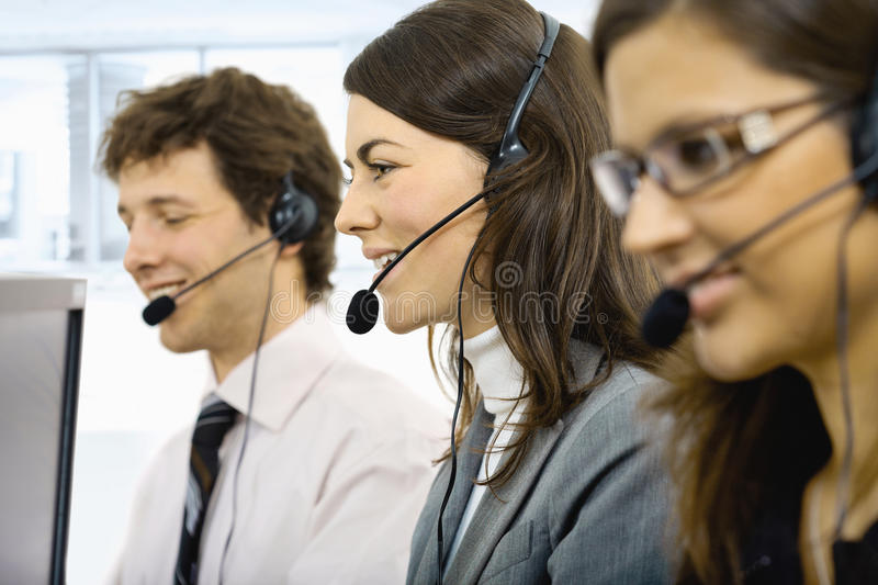 Customer service operators. Three young customer service operators sitting in a row and talking on headset. Selective focus on women in middle. Isolated on white stock images