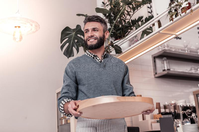 Positive cheerful man bringing order to his customers stock images