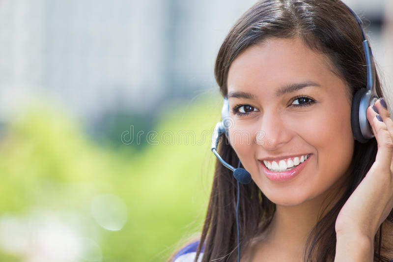 Customer service representative or call center agent or support staff or operator with headset on outside balcony stock photography