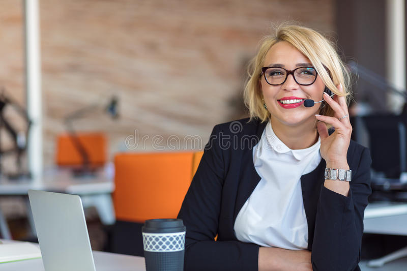 Customer service representative at work. Beautiful young woman in headset working at the computer royalty free stock images