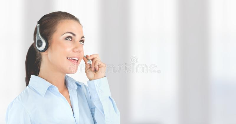 Customer service woman with bright background in call center. Digital composite of Customer service woman with bright background in call center royalty free stock image