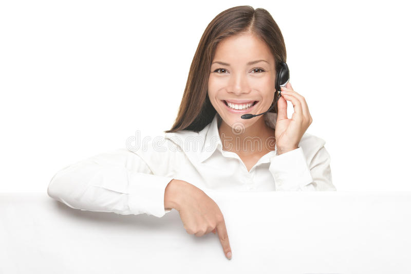 Customer Service woman showing billboard sign. Customer Service woman with headset showing and pointing at blank billboard sign banner, Young smiling Chinese stock photography
