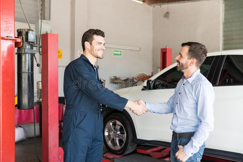 Customer Shaking Hands With Car Mechanic At Repair Shop stock photography