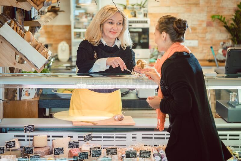 Customer and shop clerk at the cheese counter of supermarket royalty free stock photography