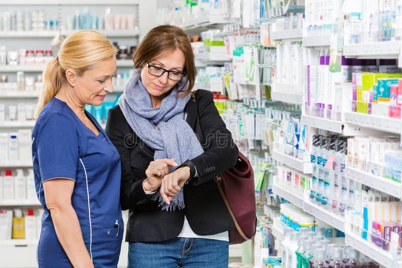 Customer Showing Medicine Information To Chemist royalty free stock photography