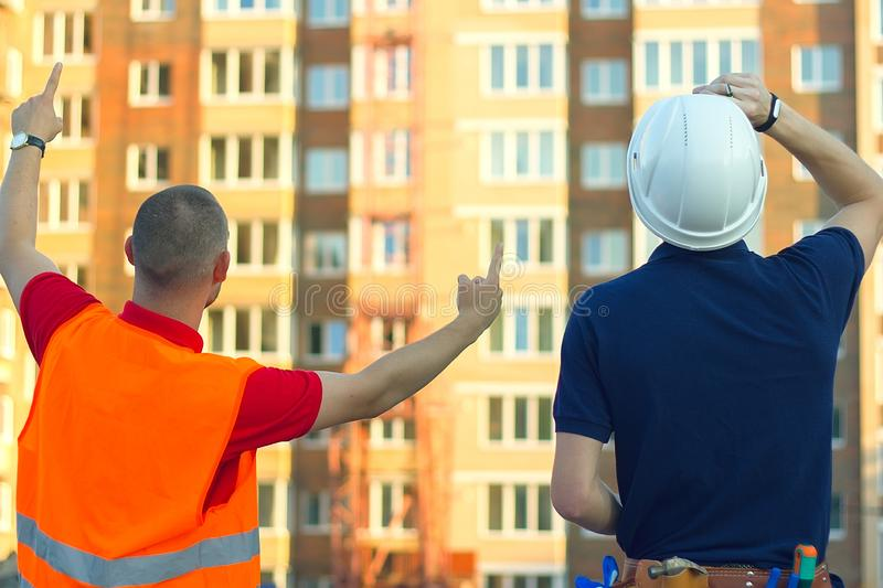 Customer in stress and constructor foreman worker with helmet and vest. Unhappy customer in stress and constructor foreman worker with helmet and vest on new royalty free stock photography