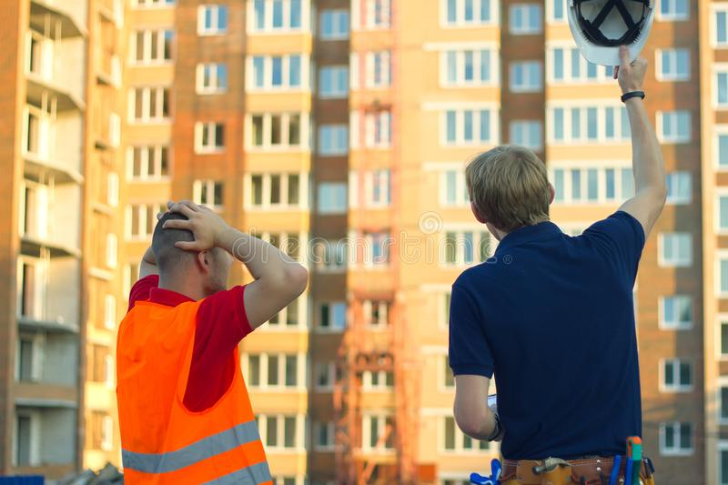 Customer in stress and constructor foreman worker with helmet and vest. Unhappy customer in stress and constructor foreman worker with helmet and vest on new stock images