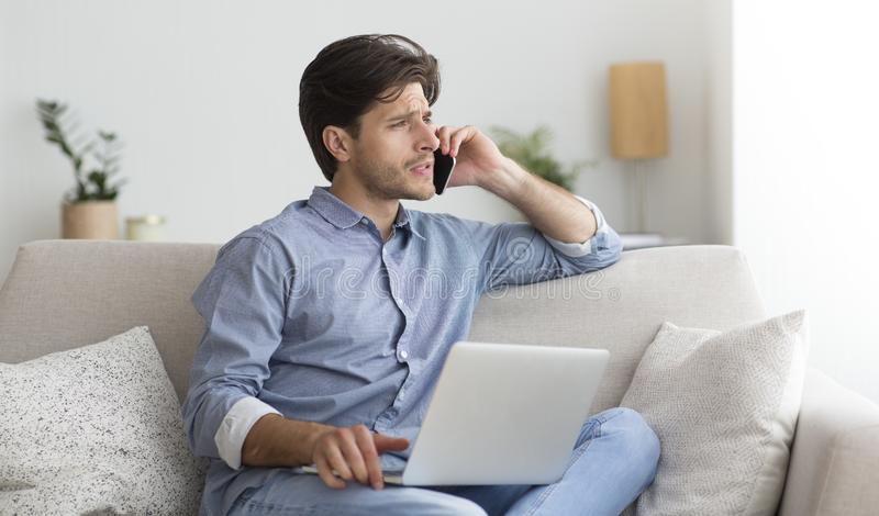 Discontented Man Complaining By Phone Sitting On Couch At Home. Customer Support Concept. Discontented Man Complaining By Phone About Bad Service Sitting On royalty free stock photo