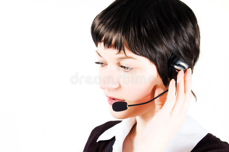 Customer support girl in call center. With headphones and microphone. Carefully listening to the customer. Hand on headphone stock photos