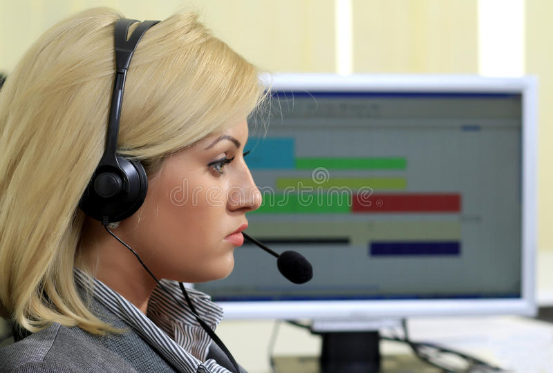 Customer support operator in the call center. Young girl operator talking on the headset's microphone in a customer support call center royalty free stock photography