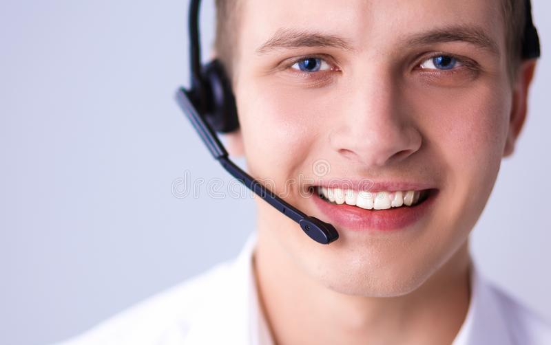 Customer support operator with a headset on white background. Call center male operator on gray background stock photography