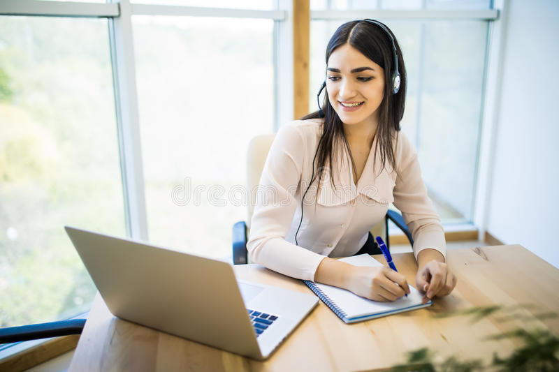 Customer support operator working in a call center office with laptop royalty free stock image