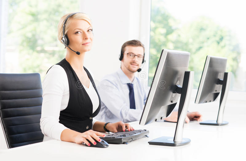 Customer support operators in formalwear working in a call center stock photo