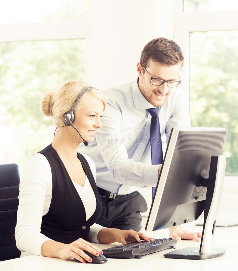 Customer support operators in formalwear working in call center stock image