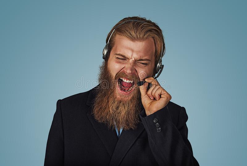 Customer support phone operator with headset yelling. Angry Bearded hipster businessman aggressive customer support phone operator with headset, he is yelling royalty free stock photos