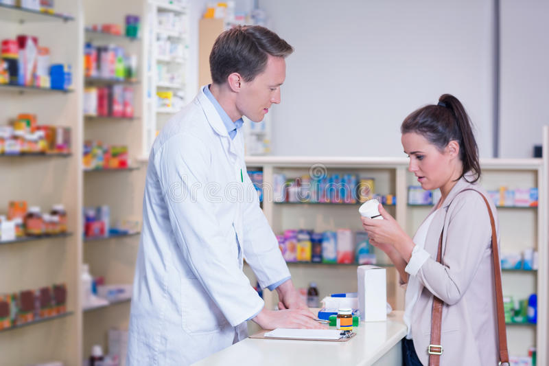 Customer talking to a pharmacist while holding a box of pills stock photography