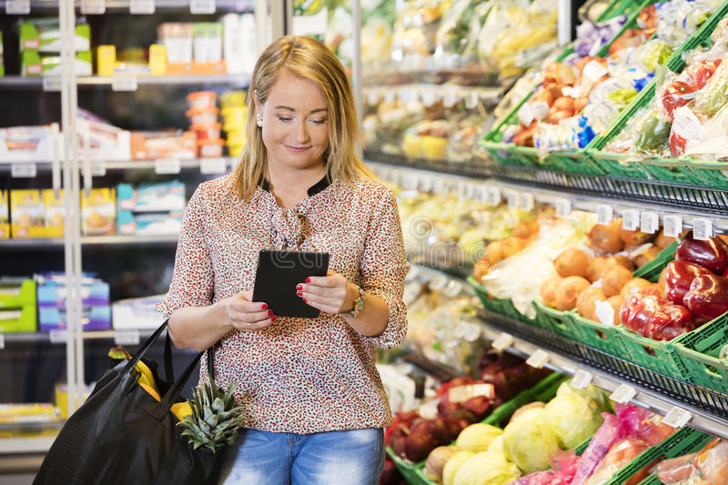 Customer Using Digital Tablet While Shopping In Grocery Store. Mature female customer using digital tablet while shopping in grocery store royalty free stock image