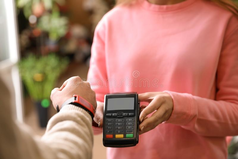 Customer using terminal for contactless payment with smartwatch in floral shop. Closeup stock images