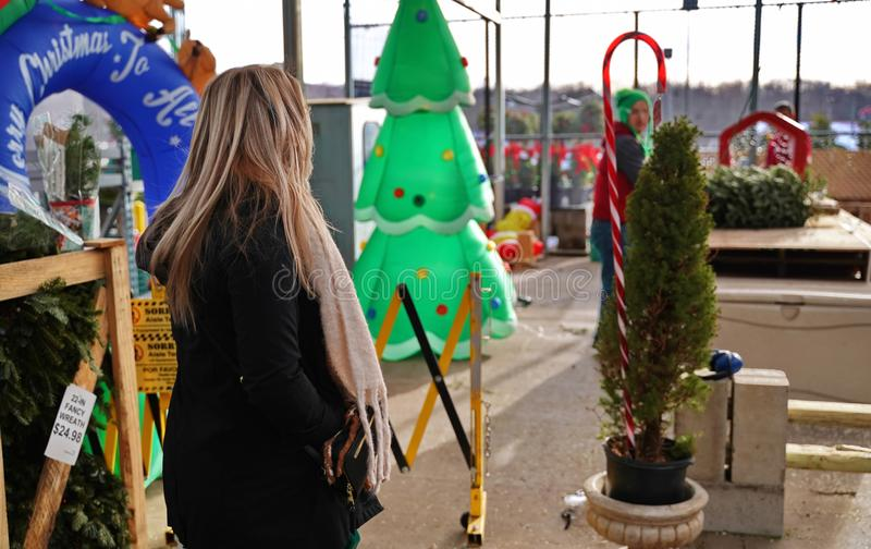 Customer waiting for tree to be netted. Cromwell, CT USA. Dec 2019. Customer waiting for store employee to net her Christmas tree stock image