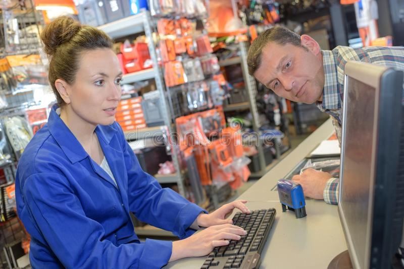 Customer watching sales clerk on computer. Retail royalty free stock photography