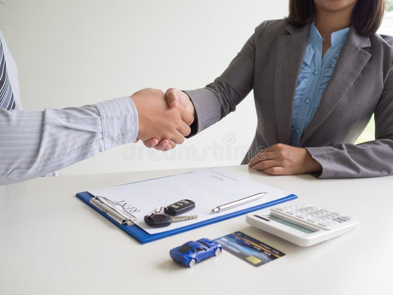 Customer woman used credit card and signed for rent car form salesman, Shake hands deal business stock image