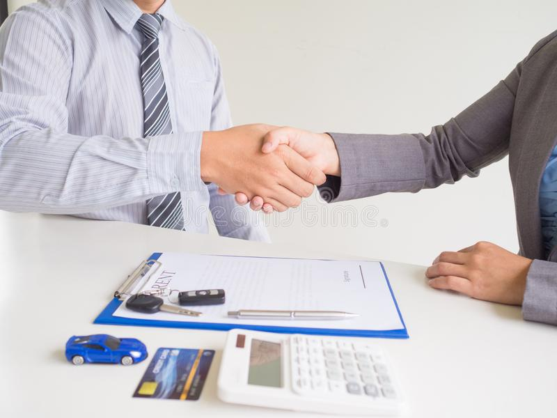 Customer woman used credit card and signed for rent car form salesman, Shake hands deal business royalty free stock photo