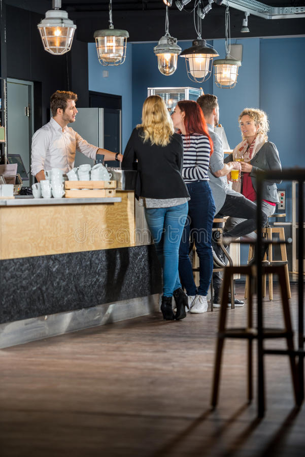 Customers With Bartender Standing At Counter. Male and female customers with bartender standing at counter in bar royalty free stock photos