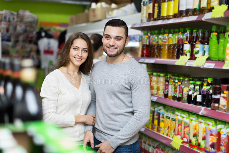 Customers at beverages section of supermarket. Portrait of young happy customers standing at beverages section of supermarket royalty free stock photo