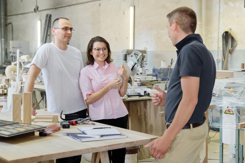 Customers and a carpentry workshop engineer discussing wooden products.  royalty free stock photography
