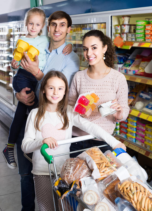 Customers with children selecting sweet dairy products in hyper stock photos