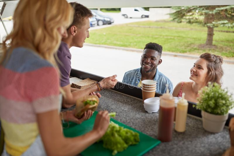 Customers couple ordering hamburgers at food truck. Street sale, eating and people concept - happy customers couple ordering hamburgers at food truck royalty free stock image