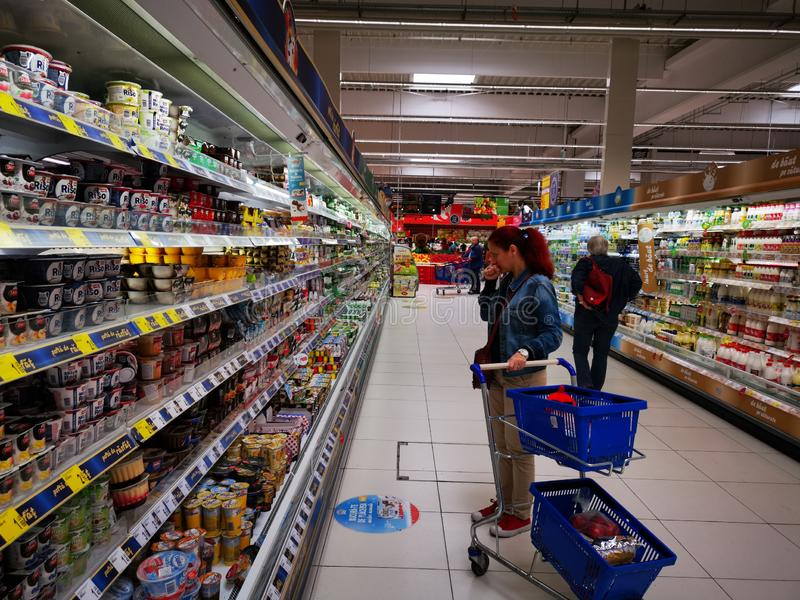 Customers at dairy and cheese shelves in supermarket Carrefour. Romania. Carrefour is a French multinational company, being one of the largest retailers in the stock images