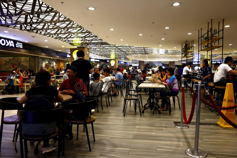 Customers eat their meal at a food court of a commercial shopping center. QUEZON CITY, PHILIPPINES – AUGUST 25, 2019: Customers eat their meal at a food stock photo