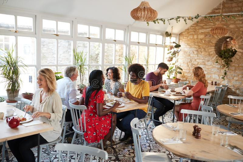 Customers eating at a busy restaurant in the day time royalty free stock image