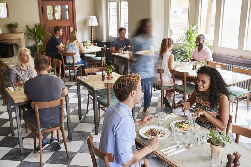 Customers Enjoying Meals In Busy Restaurant stock photo