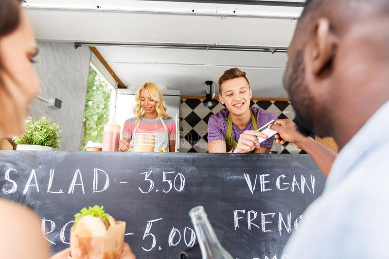 Customers giving credit card at food truck seller. Street sale, payment and people concept - happy customers giving credit card at food truck seller royalty free stock photo