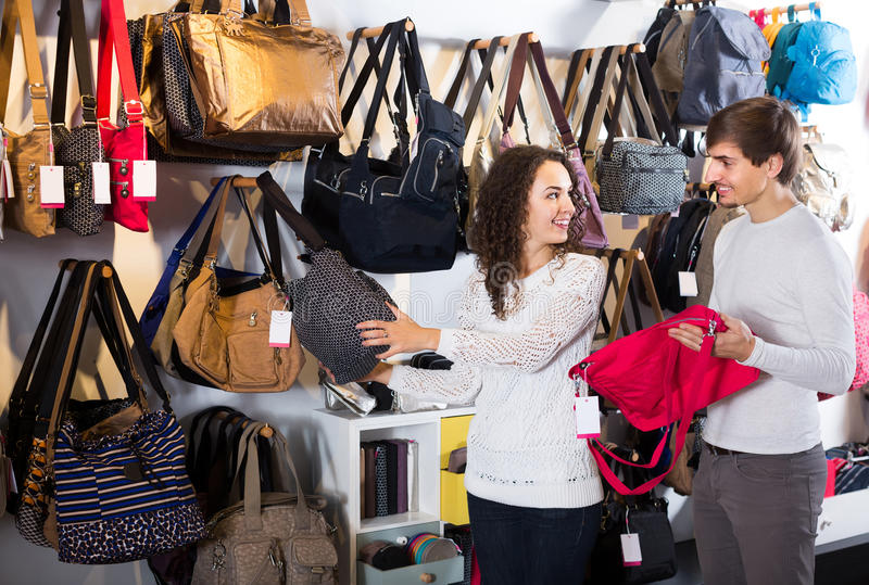 Customers looking at stylish female handbags in store stock photography